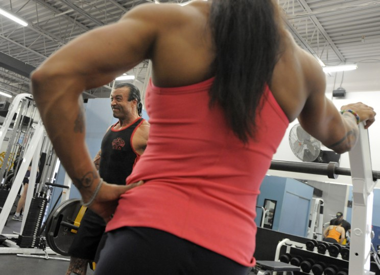 Nikki Johnston, foreground, watches as her husband David works out at a gym in Columbia. They are preparing for an upcoming competition. (Lloyd Fox/Baltimore Sun)