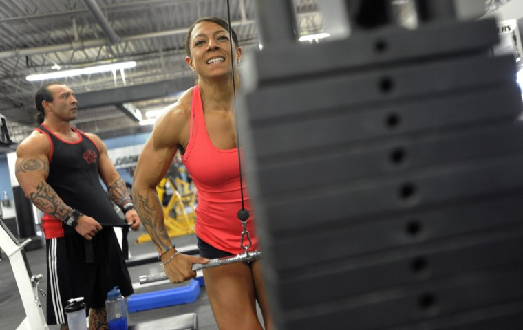 Nikki Johnston lifts weights as she works out in preparation for competition. In the background at left is her husband David, who is also a competitive bodybuilder. (Lloyd Fox/Baltimore Sun)