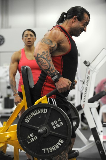 Nikki Johnston, in background, watches as her husband David works out at the Colosseum Gym in Columbia. (Lloyd Fox/Baltimore Sun)