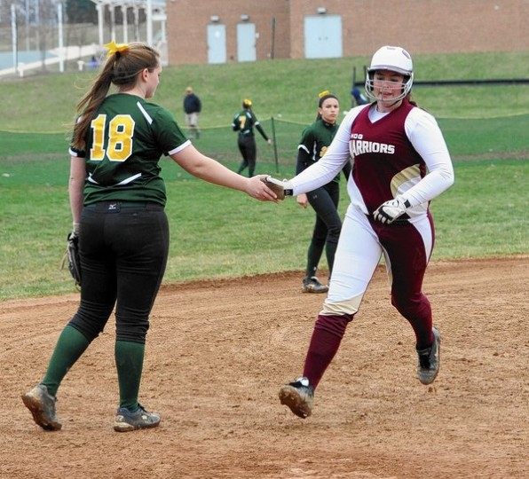 In a show of good sportsmanship, North Harford's Alexis Lyttle, left, slaps hands with Havre de Grace's Megan Thompson, congratulating Thompson on a home run during a county softball game at North Harford Friday, April 4. (Matt Button/BSMG)