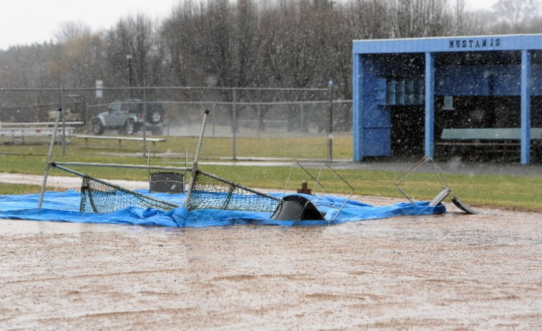 Tarps cover the base areas on the baseball field at C. Milton Wright High School as rain continues to come down and even change to snow late Sunday afternoon. (Matt Button/BSMG)
