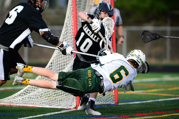 Wilde Lake's Ryan Tiffey, center, dives while making a shot on net during a boys lacrosse tournament game on Saturday, April 19. (Matt Hazlett/BSMG)