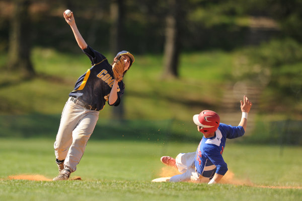 Catonsville's Lee Wolfe thows to first in an attempt to turn a double play after forcing out Lansdowne base runner David Miller during a baseball game at Catonsville High School on Thursday, April 24. (Brian Krista/BSMG)