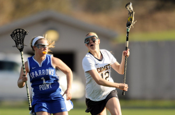 Catonsville's Jenn Nonn, right, sprints up the sidelines with the ball, hoping to outrace Sparrows Point's Katie Barth during a girls lacrosse game at Catonsville High School on Wednesday, April 23. (Brian Krista/BSMG)