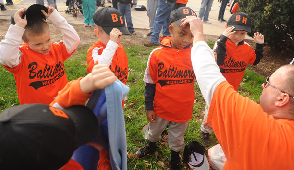Coach Jeff Borman, right, helps his Baltimore-Highlands T-Ball players as they try on their hats for the first time before the Baltimore-Highlands, Lansdowne and Riverview Little League Opening Day Parade on Saturday, April 19. (Brian Krista/BSMG)