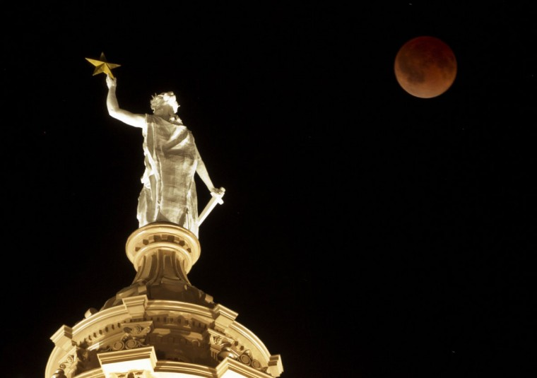 The moon turns red during a total lunar eclipse over the Goddess of Liberty statue atop the Capitol in Austin, Texas. (Jay Janner/Austin American-Statesman/MCT)
