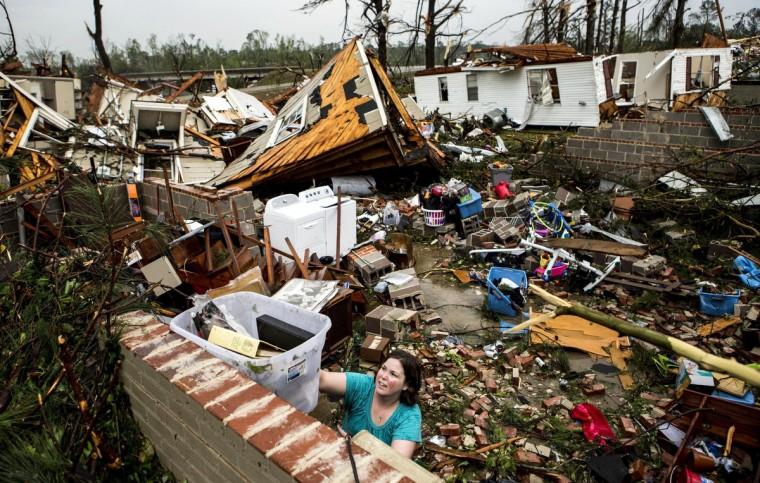 Jodi Walls pushes a box of belongings out of a friend's house while cleaning up after a large tornado made its way along Clayton Ave in Tupelo, Miss., April 28, 2014. (Brad Vest/The Commercial Appeal)