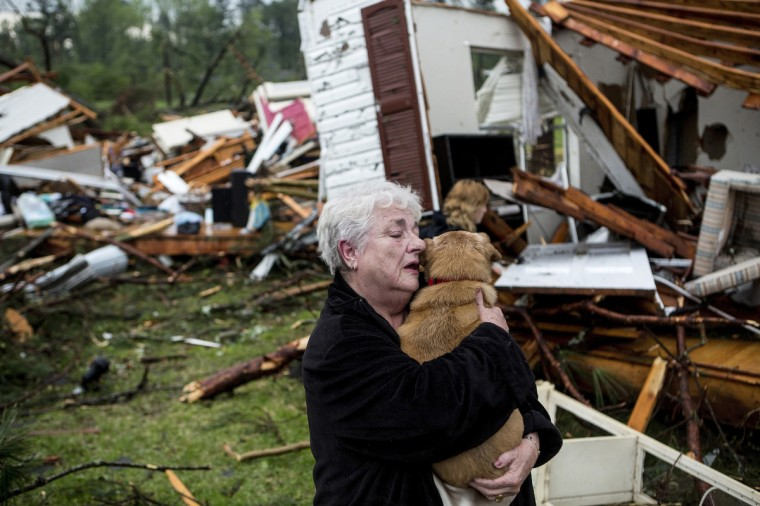 Constance Lambert embraces her dog after finding it alive when returning to her destroyed home in Tupelo, Miss., on Monday, April 28, 2014. Lambert was at an event away from her home when the tornado struck and rushed back to check on her pets. (Brad Vest/The Commercial Appeal/MCT)
