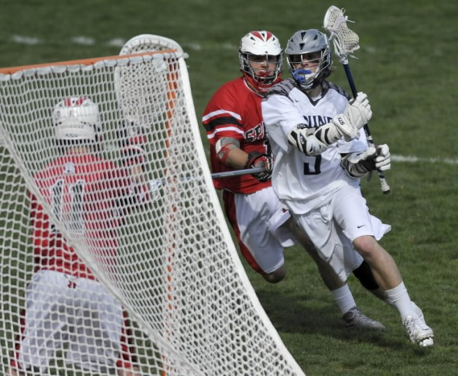 Gilman's Chase Wittich, right, drives to the goal against Spalding's Jacob Parker, center, and goalkeeper Justin Bell in the first half of a high school lacrosse game Friday, April 11 in Roland Park. (Steve Ruark/BSMG)