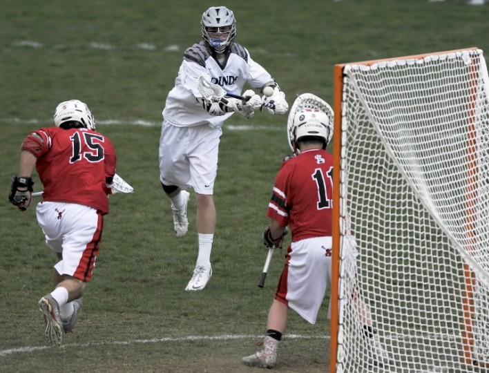 Gilman's Chase Wittich, center, shoots against Spalding's Jacob Parker, left, and goalkeeper Justin Bell in the first half of a high school lacrosse game Friday, April 11 in Roland Park. (Steve Ruark/BSMG)