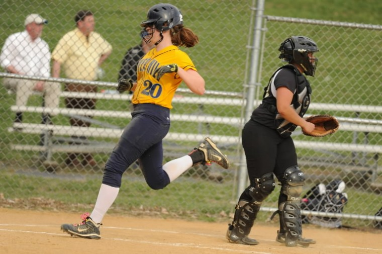 River Hill's Kallan Dirmeyer, left, passes Mt. Hebron catcher Aaliyah Montague-Bass scoring a run for the Hawks during a softball game at Mt. Hebron High School in Ellicott City on Friday, April 11. (Brian Krista/BSMG)
