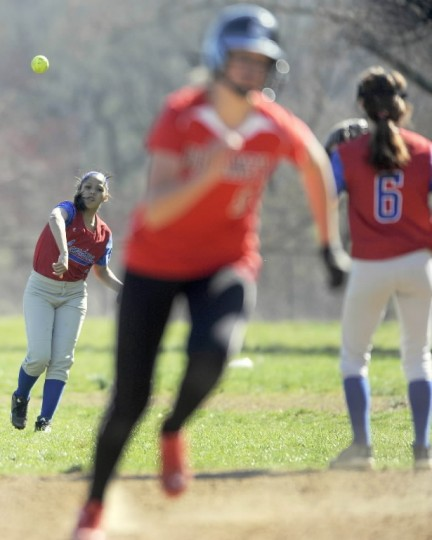 Lansdowne center fielder Silvia Cacares, left, throws to second baseman Emily Wilkens, right, as Dulaney's Ann Benzinger, center, runs to third base in the third inning of a high school softball game Thursday, April 10 in Timonium. (Steve Ruark/BSMG)
