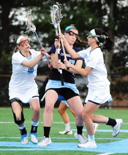 Mount de Sales' Allie Hynson, left, joins teammate Mandi Ignacio, right, in jarring the ball loose from Garrison Forest player Julie Legar during a game at Mount de Sales Academy in Catonsville on Wednesday, April 9. (Jon Sham/BSMG)