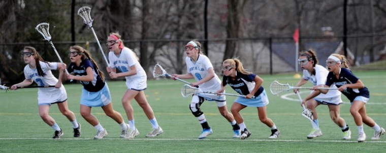 Mount de Sales' Allie Hynson, center, teammates and Garrison Forest players await the outcome of a face off during a game at Mount de Sales Academy in Catonsville on Wednesday, April 9. (Jon Sham/BSMG)