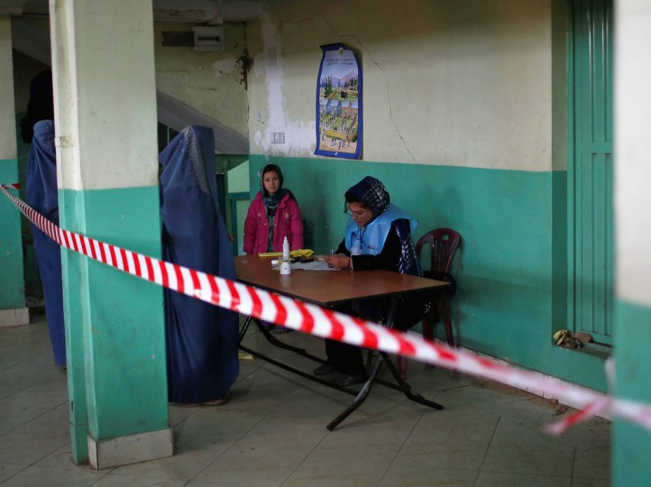 An electoral official processes voters at a polling station in Kabul April 5, 2014. Voting began on Saturday in Afghanistan's presidential election, which will mark the first democratic transfer of power since the country was tipped into chaos by the fall of the hardline Islamist Taliban regime in 2001. (REUTERS/Ahmad Masood)