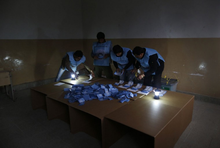 Election officials count ballot papers by lamp light after voting closed at a polling station in Kabul April 5, 2014. Voting was largely peaceful in Afghanistan's presidential election on Saturday, with only isolated attacks on polling stations as a country racked by decades of chaos embarked on its first ever democratic transfer of power. (REUTERS/Tim Wimborne)