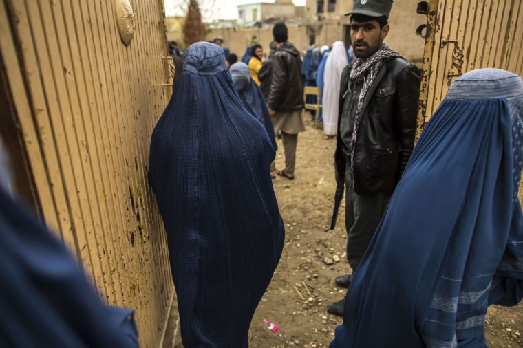 An Afghan policemen guards the entrance of a polling station in Mazar-i-sharif April 5,2014. Voting was peaceful during the first few hours of Afghanistan's presidential election on Saturday, with only isolated attacks on polling stations as the country embarked on the first democratic transfer of power since the fall of a Taliban regime in 2001. (REUTERS/Zohra Bensemra)
