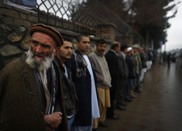 Afghans wanting to vote queue in the rain outside a polling station before it opened in Kabul April 5, 2014. Voting began on Saturday in Afghanistan's presidential election, which will mark the first democratic transfer of power since the country was tipped into chaos by the fall of the hardline Islamist Taliban regime in 2001. (REUTERS/Tim Wimborne)