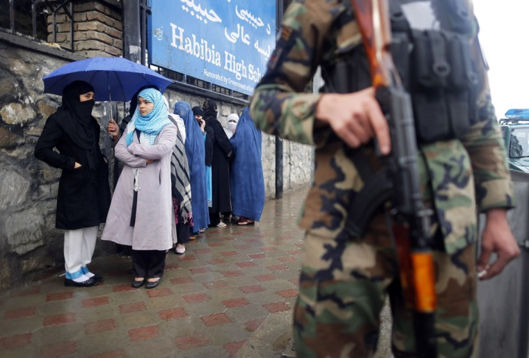 A policeman stands guard outside a polling station in Kabul as Afghans wanting to vote queue outside before it opened April 5, 2014. Voting began on Saturday in Afghanistan's presidential election, which will mark the first democratic transfer of power since the country was tipped into chaos by the fall of the hardline Islamist Taliban regime in 2001. (REUTERS/Tim Wimborne)