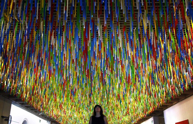Australian artist Nike Savvas inspects her artwork titled 'Rally' that hangs from the roof of the New South Wales Art Gallery April 7, 2014. Savvas says her hanging installation, which is made up of more than 60,000 colored ribbons being blown by fans, was inspired by her recent visit to Brazil and represents 'fields of color in motion that swirls and regathers like an unpredictable crowd'. (David Gray/Reuters)