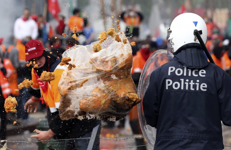 A demonstrator throws garbage towards riot police officers during a European trade unions protest against austerity measures, in central Brussels April 4, 2014. || PHOTO CREDIT: FRANCOIS LENOIR - REUTERS