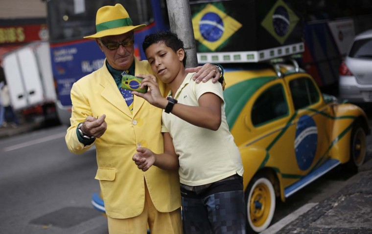 Brazilian attorney, Nelson Paviotti (R), looks at a photo that a boy took of them together, as they stand next to Paviotti's Volkswagen Beetle painted with the colors of the national flag - green, yellow, white and blue, in Campinas, Sao Paulo state, April 9, 2014. Paviotti claims he has worn clothes of only those colors as he promised to do if Brazil won the 1994 World Cup, which it did. He has recently decorated his home especially for the 2014 World Cup that Brazil is hosting. Picture taken April 9, 2014. (Nacho Doce/Reuters)