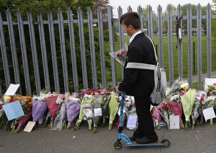 A pupil looks at floral tributes at Corpus Christi Catholic College where teacher Anne Maguire was fatally stabbed in Leeds, northern England April 29, 2014. British police have arrested a 15-year-old schoolboy after a female teacher was fatally stabbed at a school in northern England on Monday. (Darren Staples/Reuters)