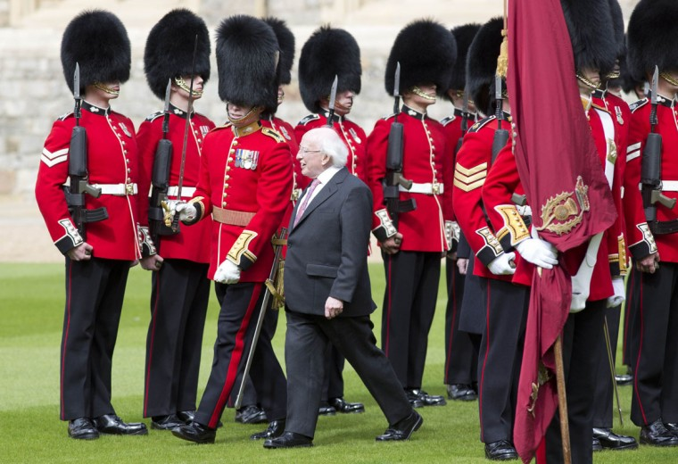 The President of Ireland Michael D. Higgins (C) inspects a Guard of Honour at Windsor Castle in Windsor, southern England April 8, 2014. The Irish President and his wife Sabina are embarking on a four day State Visit to Britain, and will stay at Windsor Castle as guests of Queen Elizabeth. (REUTERS/Neil Hall)