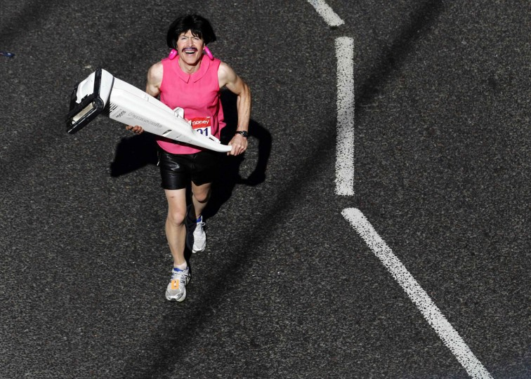 A competitor dressed as Freddie Mercury and carrying a vacuum cleaner runs for charity during the London Marathon. (Luke MacGregor/Reuters)