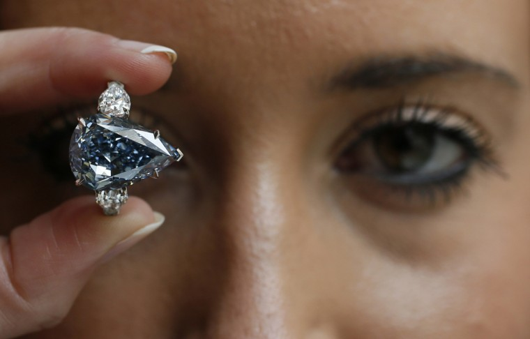 "An employee poses with ""The Blue"" diamond at Christie's auction house in London April 29, 2014. Christie's London is displaying the largest flawless fancy vivid blue diamond ever to appear at auction. The diamond is pegged at $21 million to $25 million and is the highlight of an upcoming Magnificent Jewels sale in Geneva. (Stefan Wermuth/Reuters)"