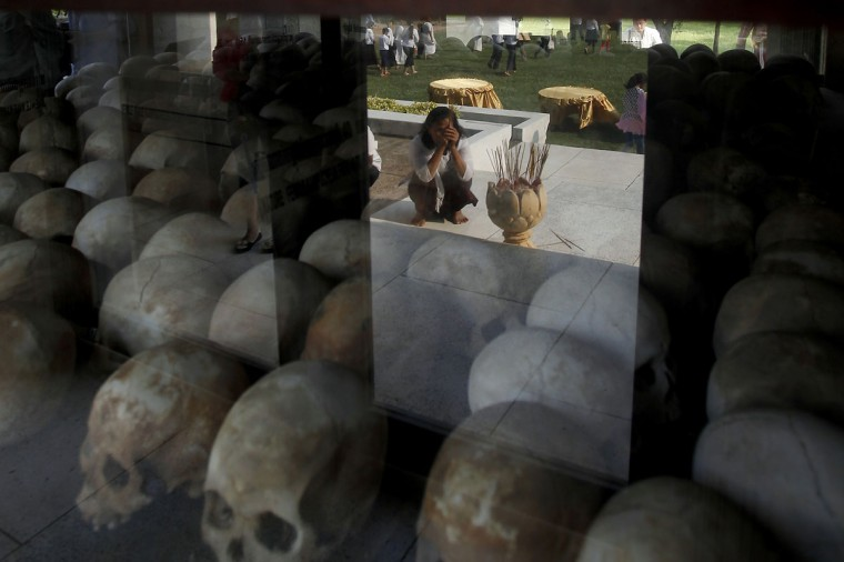 "A woman is reflected in a glass pane as she prays with incense sticks during a gathering at a memorial stupa, with bones of more than 8,000 victims of the Khmer Rouge regime, at Choeung Ek, a ""Killing Fields"" site located on the outskirts of Phnom Penh April 17, 2014. Hundreds of Cambodians and monks gathered at the site to commemorate the 39th anniversary of the Khmer Rouge reign, which plunged the nation into a radical communist group genocide regime from 1975-1979. (REUTERS/Samrang Pring)"