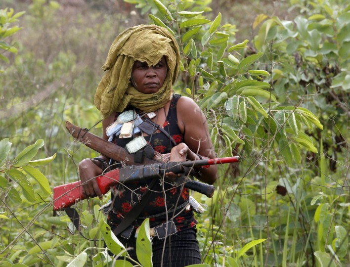 A female member of the anti-balaka, a Christian militia, patrols with other militiamen outside village of Zawa April 8, 2014. (REUTERS/Goran Tomasevic)