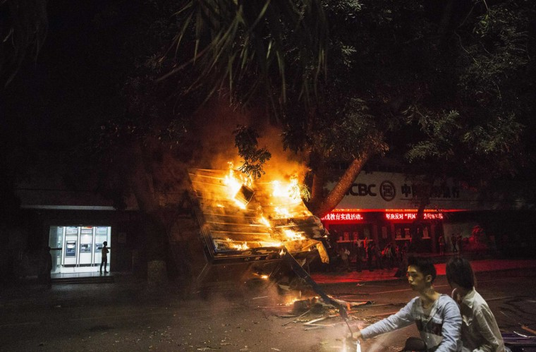 Residents ride past a burning public security kiosk during a protest against a chemical plant project, on a street in Maoming, Guangdong province, early April 1, 2014. The city in southern China which has been the site of violent protests against a proposed chemical plant said it will not go ahead with the project if a majority of residents object to it, as authorities seek to head off more unrest. (Stringer/Reuters)