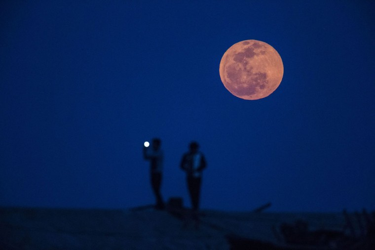 A man takes a picture during moon rise in a suburb of Shanghai (REUTERS/Aly Song)