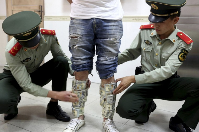 Paramilitary policemen take off U.S. dollars strapped around a man's legs, at the border of Hong Kong and Shenzhen, Guangdong province, April 24, 2014. According to local media, the man was found trying to smuggle in total of US$580,000 from mainland to Hong Kong. Picture taken April 24, 2014. (REUTERS/China Daily)