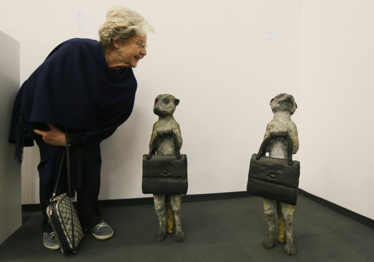 "A woman looks at bronze sculptures ""Meercat 1"" and ""Meercat 2"" by British artist Laura Ford at the ""Art Cologne"" art fair in Cologne April 9, 2014. The sculptures are on sale for 19,000 euros each. Some 200 international exhibitors are taking part in the 48th Art Cologne, one of the world's leading fairs for contemporary art. (Wolfgang Rattay/Reuters)"