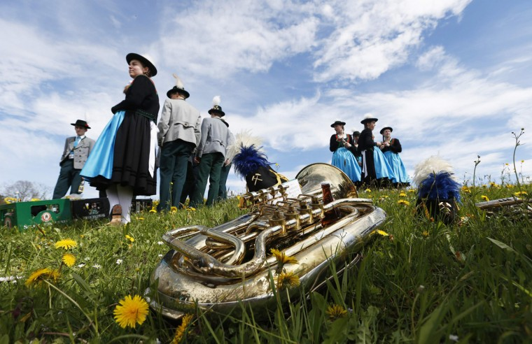 """A brass instrument lies in the grass as pilgrims dressed in traditional Bavarian clothes attend the traditional Georgi horse riding procession on Easter Monday in the southern Bavarian town of Traunstein April 21, 2014. Since the early 16th century, farmers have taken part in the pilgrimage to bless their horses. This tradition, the """"Georgiritt"""", goes back to the legend of Saint George, the horsemen's patron saint. (Michaela Rehle/Reuters)"""