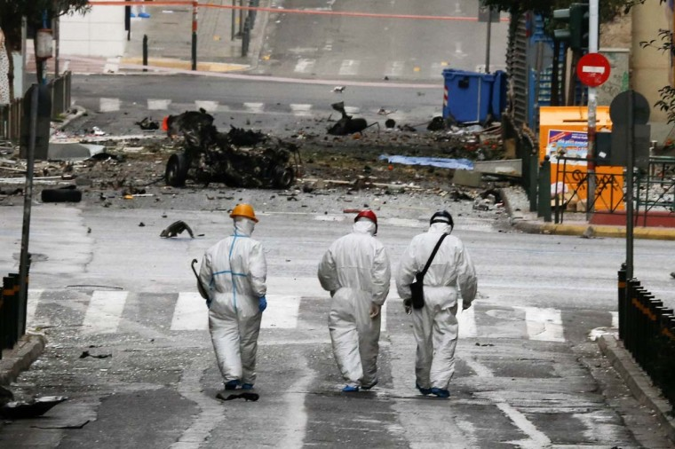 Forensic experts search for evidence on a street where a car bomb went off in Athens April 10, 2014. The car bomb went off outside a Bank of Greece building in central Athens early on Thursday, smashing windows in nearby shops but causing no injuries, police and Reuters witnesses said. The blast struck hours before Greece planned its first foray into the international bond markets since it plunged into a debt crisis four years ago, and a day before a visit by German Chancellor Angela Merkel. (Alkis Konstantinidis/Reuters)