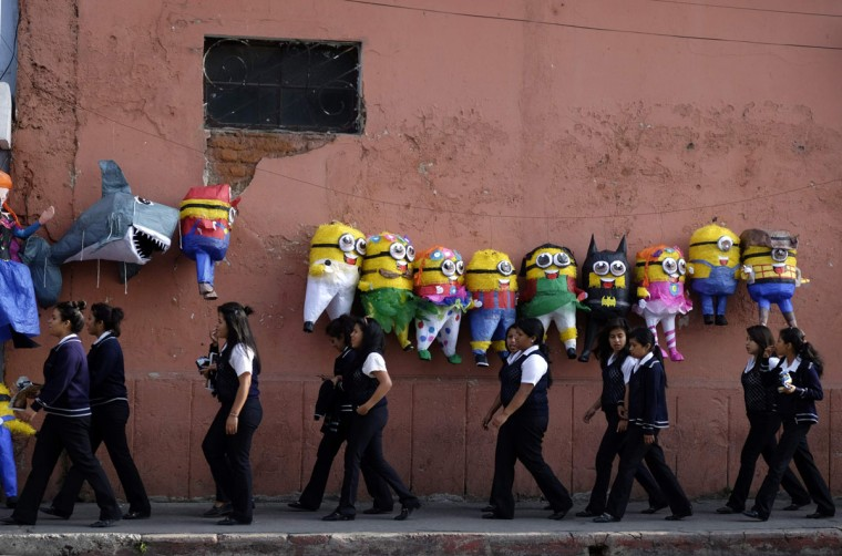 "College students walk past below pinatas, including those in the shape of Minions from the movie ""Despicable Me"", along a street in downtown Guatemala City, April 7, 2014. (REUTERS/Jorge Dan Lopez)"
