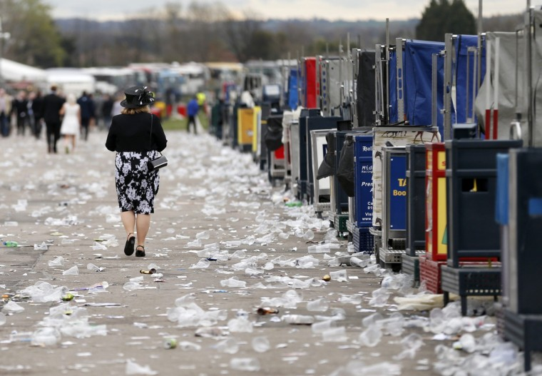 A racegoer walks through litter on her way past the betting stands at the end of Ladies' Day at the Grand National horse racing meeting at Aintree, northern England. (Russell Cheyne/Reuters photo)