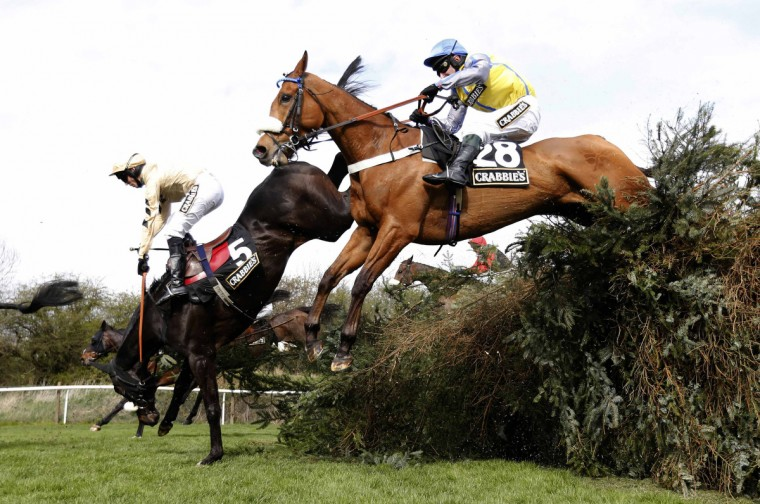 Fago (L), ridden by Barry Fehilly, falls at the open ditch in the 'Supporting The Everton In The Community Steeple Chase' during the Grand National horse racing meeting at Aintree, northern England. (Russell Cheyne/Reuters photo)