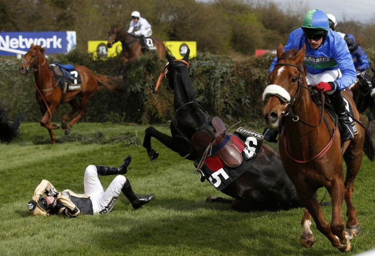 Fago, ridden by Barry Fehilly, falls at the open ditch at the 'Supporting The Everton In The Community Steeple Chase' during the Grand National horse racing meeting at Aintree, northern England. (Russell Cheyne/Reuters photo)