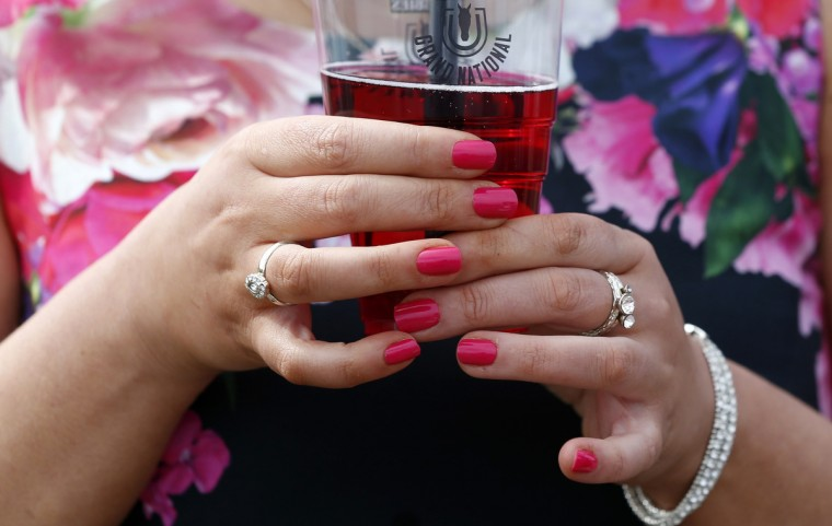 A racegoer holds a drink on Ladies' Day, the second day of the Grand National horse racing meeting at Aintree, northern England. (Russell Cheyne/Reuters photo)