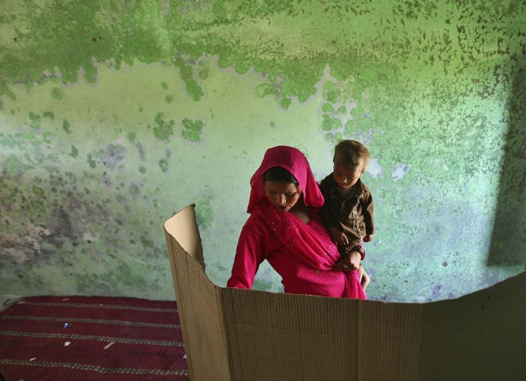 A woman holding her child votes for the general election inside a polling station on the outskirts of Jammu April 10, 2014. Around 815 million people have registered to vote in the world's biggest election - a number exceeding the population of Europe and a world record - and results of the mammoth exercise, which concludes on May 12, are due on May 16. (Mukesh Gupta/Reuters)
