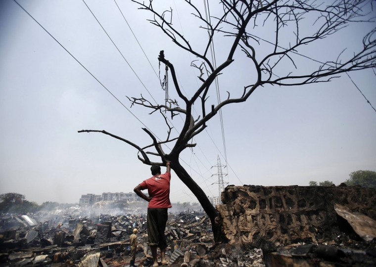 A resident stands next to the debris of huts after a fire broke out in a slum area in New Delhi April 25, 2014. Hundreds of huts were gutted in the fire but no casualties were reported and the cause of the fire was unknown, slum dwellers said on Friday. (REUTERS/Anindito Mukherjee)
