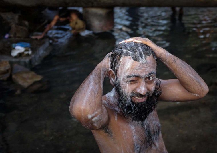 A man bathes under a broken water pipeline at a slum in Mumbai April 10, 2014. (Danish Siddiqui/Reuters)