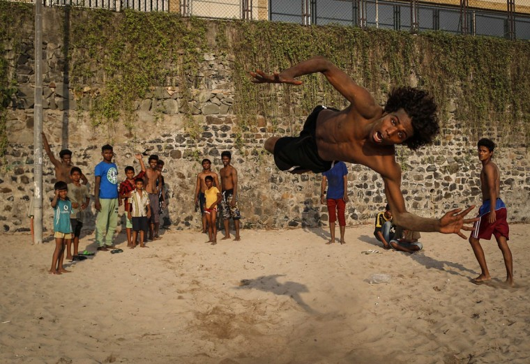 "Saddam, 19, practices stunts at a beach along the Arabian Sea in Mumbai April 25, 2014. Saddam, belongs to a small group called ""The Scrolls"" who travel from the far northern suburbs of Mumbai to the city on to perform breakdancing and other stunts in marriages parties and other events. (REUTERS/Danish Siddiqui)"