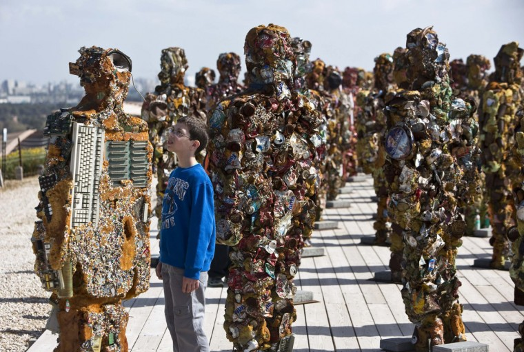 """A boy looks at a statue by German artist HA Schult during a preview of the artist's exhibition at the Ariel Sharon Park near Tel Aviv. Schult's """"Trash People"""" exhibition, featuring 500 human-sized figures made from recycled materials, has been travelling worldwide for 18 years and opens this weekend near Tel Aviv. (Nir Elias/Reuters)"""