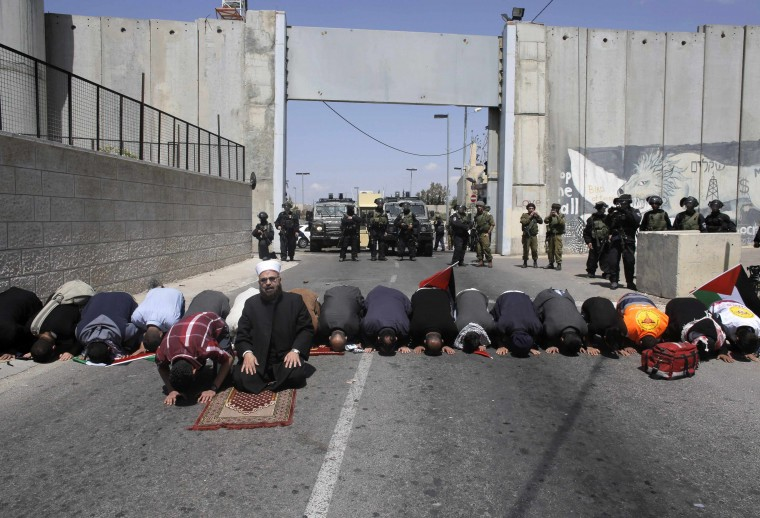 Palestinians attend Friday prayers in front of Israeli troops during a protest calling for the release of Palestinian prisoners held in Israeli jails, near an Israeli checkpoint in the West Bank town of Bethlehem. Israel has called off a planned release of Palestinian prisoners meant to advance the U.S.-sponsored peace process and called for a review of how the troubled negotiations can make progress, an official briefed on the talks said on Thursday. || PHOTO CREDIT: AMMAR AWAD - REUTERS