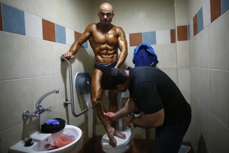 A bodybuilder stands in a toilet stall as he has toner applied backstage before an amateur competition in the Israeli city of Dimona, April 3. || PHOTO CREDIT: FINBARR O'REILLY - REUTERS